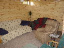 Family room on lower walkout level of Alpine Snow Cabin. Features queen size futon sofa sleeper, leather rocker recliner, love seat, TV with VCR and DVD player. Directv Satellite.