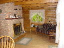 View of living room and fireplace on the main floor of Alpine Snow Cabin.
